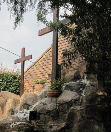 Fountain And Cross In Prayer Garden